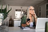 Happy senior woman holding smartphone and laptop daydreaming while looking away. Successful stylish  poster