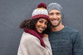 Young multiethnic couple in warm clothing looking at camera on a winter day isolated on gray wall wi poster