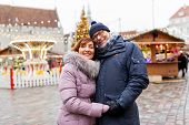 love, winter holidays and people concept - happy senior couple hugging at christmas market on town h poster