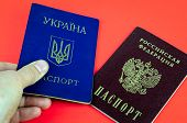 Two National Internal Passports On Red Background, Lying Red Russian Passport And Blue Ukrainian Pas poster