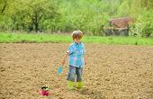 Boy Planting Flower In Field Digging Ground. Work At Farm. Mother Nature Concept. Planting Seedlings poster