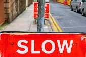 Big Red Slow Traffic Sign Warning In City poster