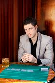 Latin handsome gambler man in table playing poker cards and drinking whiskey