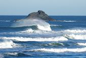 stock photo of end rainbow  - Off shore island rock with rainbow surf Roads End Beach Lincoln City Oregon - JPG