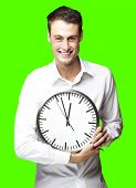 portrait of a young man holding a clock against a removable chroma key background