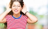 Young beautiful woman wearing glasses Trying to hear both hands on ear gesture, curious for gossip.  poster