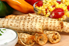picture of flauta  - Stack of chicken taquitos with hot sauce and sour cream in kitchen or restaurant - JPG