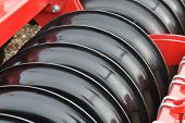 foto of cultivator-harrow  - farm equipment red and black Harrow Close up - JPG