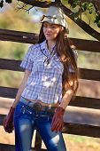 beautiful cowgirl in stetson next to wooden fence