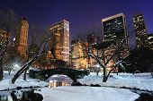 New York City Manhattan Central Park panorama in winter with snow, bridge; freezing lake and skyscra
