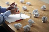 stock photo of frustrated  - Tearing up another crumpled paper ball for the pile - JPG