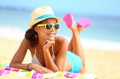 Beach woman funky happy and colorful wearing sunglasses and beach hat having summer fun during trave