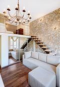 Modern style two-high living-room interior with staircase and stone wall
