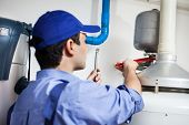 stock photo of pipe wrench  - Plumber repairing an hot - JPG