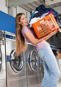 Side view of young woman carrying heavy basket of clothes in laundromat
