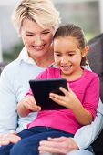 image of grandma  - cute little girl using tablet pc with grandma at home - JPG