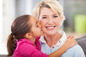 stock photo of granddaughters  - loving cute granddaughter kissing her grandmother at home - JPG