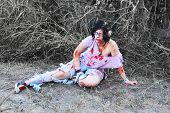 stock photo of gruesome  - Woman pretending to be a zombie sits on a road - JPG