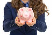 Closeup On Business Woman Showing Piggy Bank