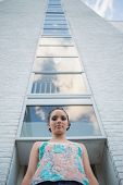 Attractive woman standing in front of a tall building and looking at camera