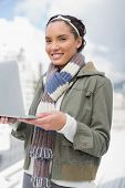 Attractive woman standing outside and holding laptop while looking at camera