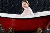 Drenched girl in a blouse sitting in the bathtub under the spray of water