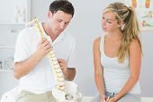 Handsome physiotherapist showing patient something on skeleton model in bright office