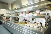 Four chefs working in a big kitchen at service time
