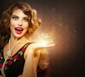 Retro Woman Portrait. Surprised Luxury Lady with Holiday Magic Gift in her Hand. Miracle Light. Copy