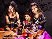 Children on Halloween party  sitting at trick or treat table.