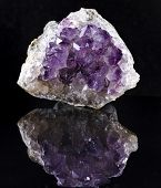 Single Natural cluster of Amethyst, violet variety of quartz close up macro with reflection on black background