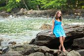 Teengirl in a blue dress in the rocks of the coast.