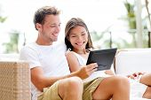 Couple relaxing together in sofa with tablet computer pc having fun. Romantic young happy multiracial couple in love sitting at home in sofa resting having fun maybe watching movie. Man and woman.