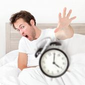 Man waking up late for work early throwing alarm clock. Funny bed concept with young man oversleeping.
