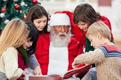 Children and Santa Claus reading book in courtyard