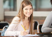 Portrait of beautiful college student sitting at desk in classroom