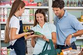 Saleswoman assisting couple in buying groceries at supermarket