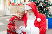 Santa Claus and boy using digital tablet together in courtyard