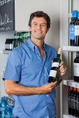 Portrait of confident mid adult man displaying wine bottle in supermarket