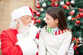 image of nicholas  - Santa Claus gesturing finger on lips at girl in front of Christmas tree - JPG