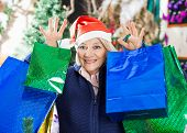 Portrait of shopaholic senior woman with shopping bags standing at Christmas store