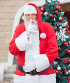 Portrait of senior man dressed as Santa Claus with finger on lips against Christmas tree