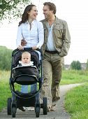 Happy Mother And Father Smiling And Pushing Baby Pram With Child