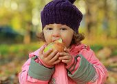 Happy Child Eating Big Red Apple On Autumn Bright Background