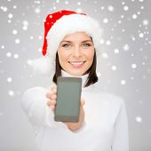 christmas, x-mas, electronics, gadget concept - smiling woman in santa helper hat with blank screen smartphone