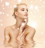 health, spa, beauty concept - face, hands and shoulders of beautiful woman