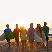 Surfers teen boys and girls group walking on beach at sunshine sunset backlight