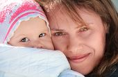 Young European Woman Holds Her Sleepy Baby In Blanket. Outdoor Closeup Portrait