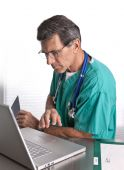 pic of doctors office  - Male Doctor working at his laptop - JPG
