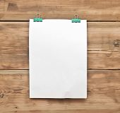 white blank note paper and paper clip on wood background